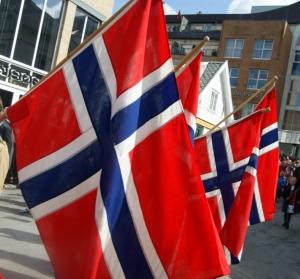 Bilde av flagg i 17. mai toget. Jeg blir stresset av folkehavet på 17. mai, men det er samtidig forunderlig tiltrekkende.
