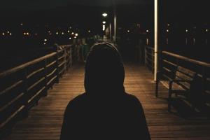 person i hettegenser sett bakfra på ei mørk gate. Det er lett å tenke negativt om denne personen.